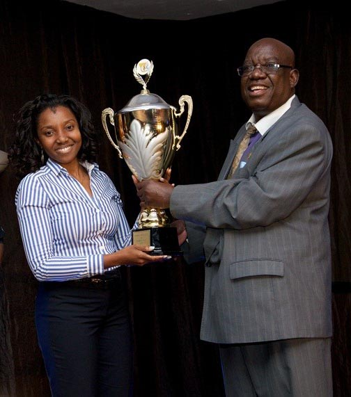 DBMN Communication Manager receiving the Trophy from Chamber of Mines President Kombandayendu Kapwanga.